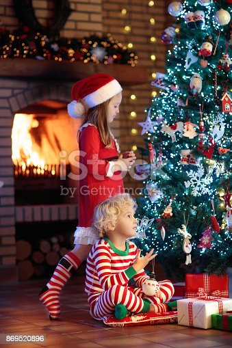 869520896 istock photo Child at Christmas tree. Kids at fireplace on Xmas 869520896