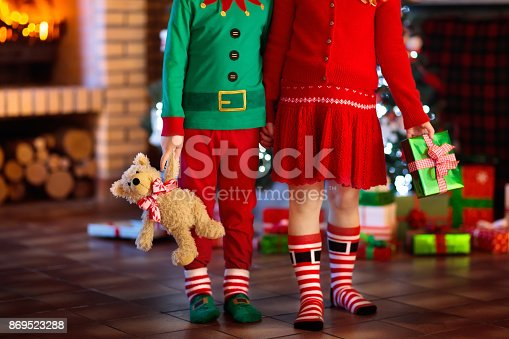 869520896 istock photo Child at Christmas tree. Kids at fireplace on Xmas 869523288