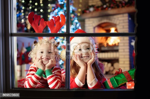 885695138 istock photo Child at Christmas tree. Kids at fireplace on Xmas 869523600