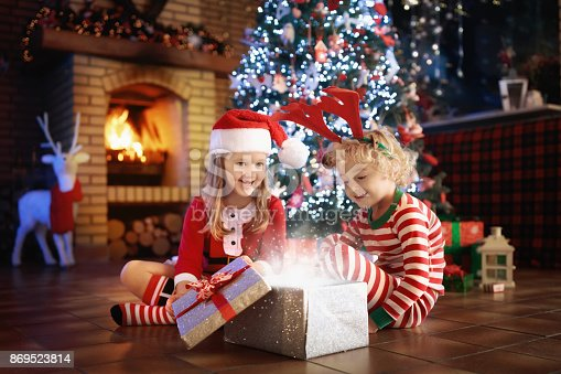 885695138 istock photo Child at Christmas tree. Kids at fireplace on Xmas 869523814