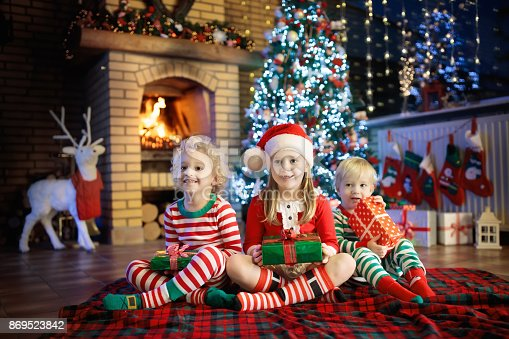 869520896 istock photo Child at Christmas tree. Kids at fireplace on Xmas 869523842