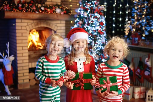 885695138 istock photo Child at Christmas tree. Kids at fireplace on Xmas 869524014