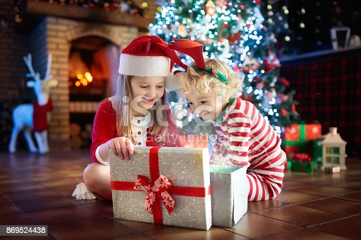 869520896 istock photo Child at Christmas tree. Kids at fireplace on Xmas 869524438