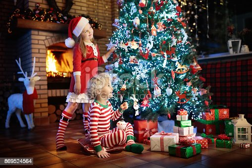 885695138 istock photo Child at Christmas tree. Kids at fireplace on Xmas 869524564