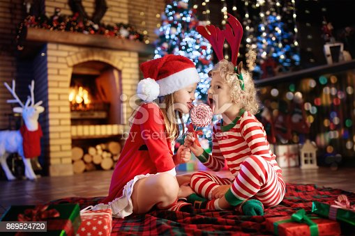 885695138 istock photo Child at Christmas tree. Kids at fireplace on Xmas 869524720