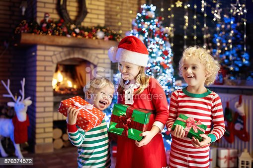 869520896 istock photo Child at Christmas tree. Kids at fireplace on Xmas 876374572