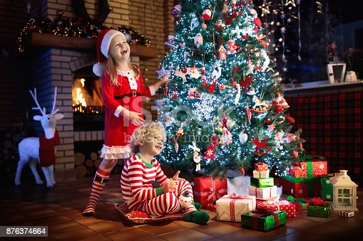 869520896 istock photo Child at Christmas tree. Kids at fireplace on Xmas 876374664
