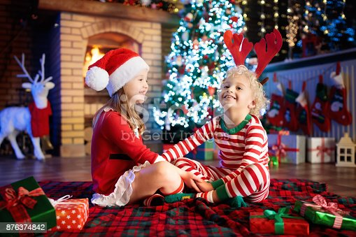 869520896 istock photo Child at Christmas tree. Kids at fireplace on Xmas 876374842