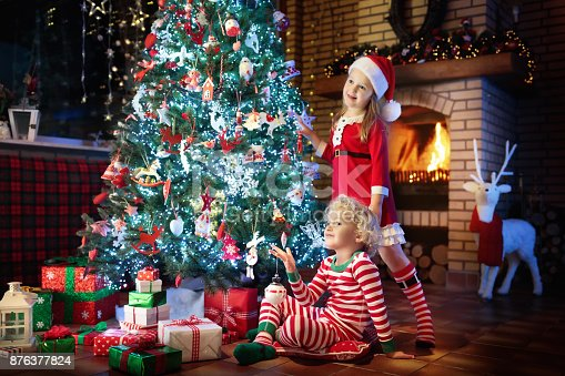 869520896 istock photo Child at Christmas tree. Kids at fireplace on Xmas 876377824