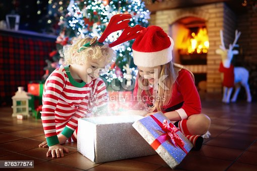 869520896 istock photo Child at Christmas tree. Kids at fireplace on Xmas 876377874