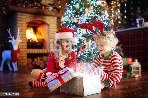 885695138 istock photo Child at Christmas tree. Kids at fireplace on Xmas 876378208