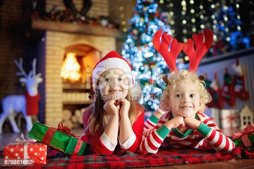 885695138 istock photo Child at Christmas tree. Kids at fireplace on Xmas 876381882