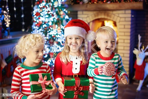 869520896 istock photo Child at Christmas tree. Kids at fireplace on Xmas 876382456