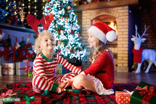 869520896 istock photo Child at Christmas tree. Kids at fireplace on Xmas 876497466