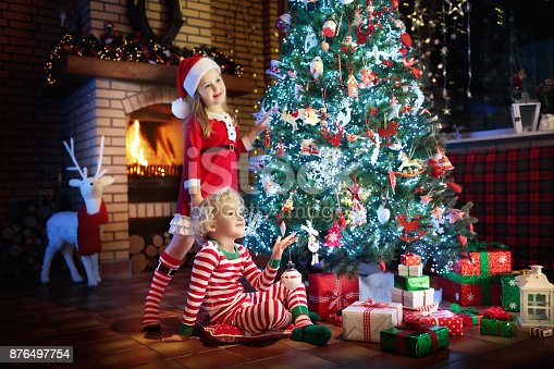 869520896 istock photo Child at Christmas tree. Kids at fireplace on Xmas 876497754