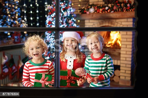 885695138 istock photo Child at Christmas tree. Kids at fireplace on Xmas 877876304