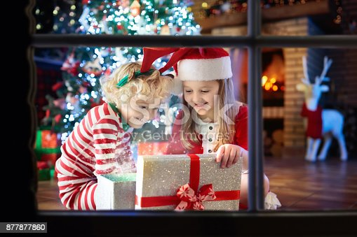 869520896 istock photo Child at Christmas tree. Kids at fireplace on Xmas 877877860