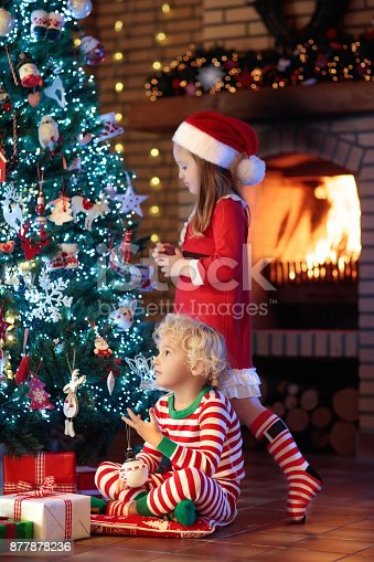 869520896 istock photo Child at Christmas tree. Kids at fireplace on Xmas 877878236