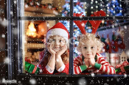 869520896 istock photo Child at Christmas tree. Kids at fireplace on Xmas 885698226