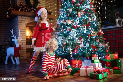869520896 istock photo Child at Christmas tree. Kids at fireplace on Xmas 885704480