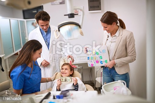 Happy child at dentist hold greenback for luck