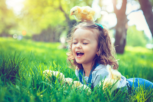 Little girl celebrating Easter outdoors with chicken
