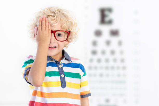 Child at eye sight test. Kid at optitian. Eyewear for kids. stock photo