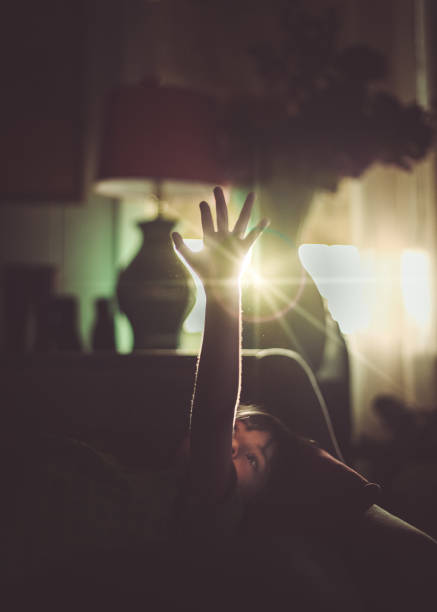 Child at home raising hand up to sunbeam ethereal stock photo