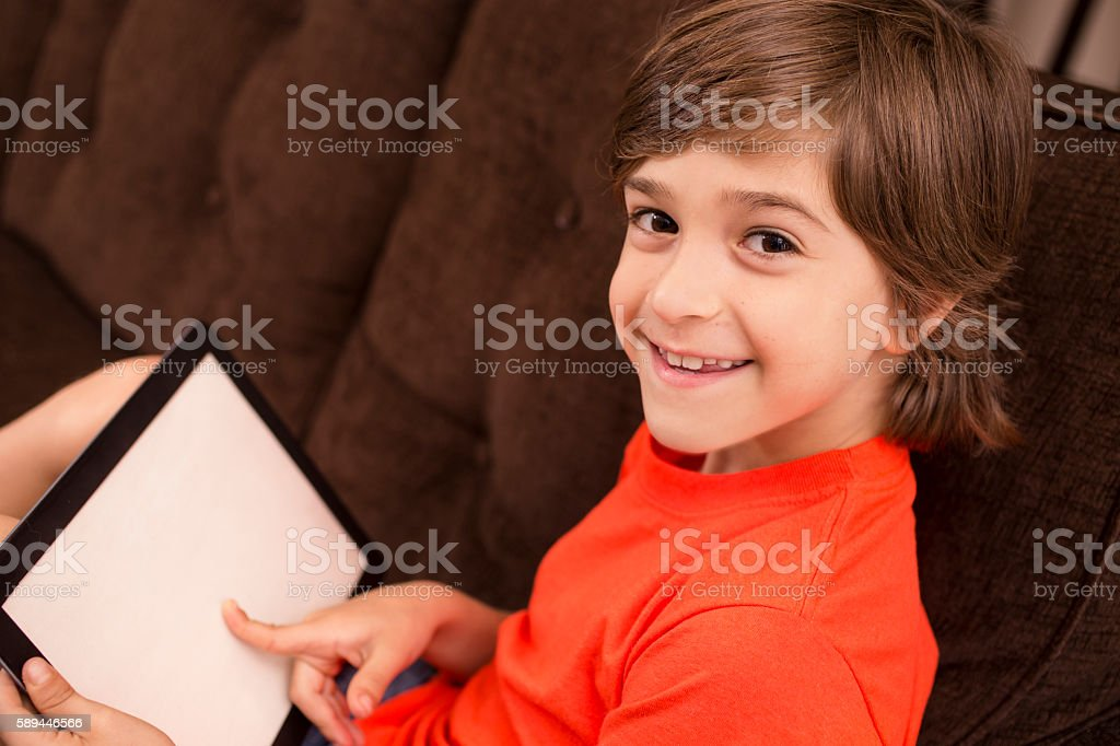 Child at home reading digital tablet on sofa. stock photo
