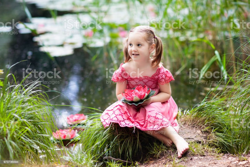 Child at lake with water lily flowers. stock photo