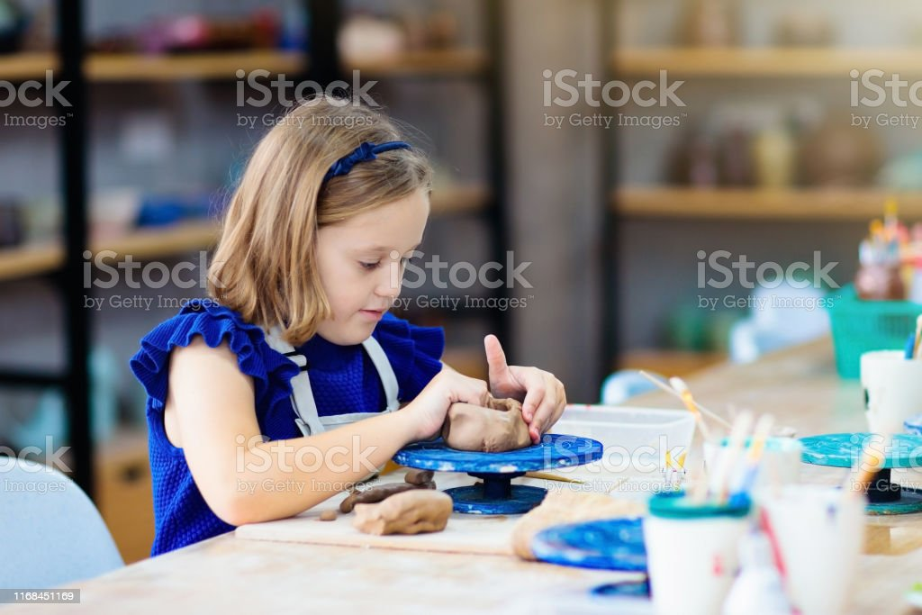 Child working on pottery wheel. Kids arts and crafts class in...