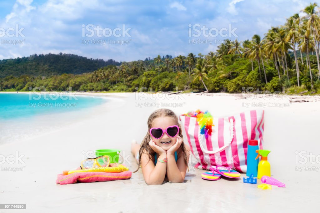 Child at tropical beach with bag and toys. stock photo