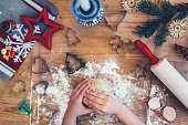 overhead view on little girls hands kneading dough for christmas cookies on wooden board
