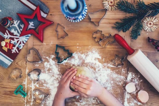 Kind backt Weihnachtsplätzchen auf Holztisch – Foto