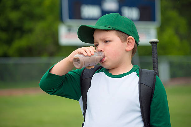 Child baseball player drinking chocolate milk Child baseball player drinking chocolate milk after game chocolate milk stock pictures, royalty-free photos & images
