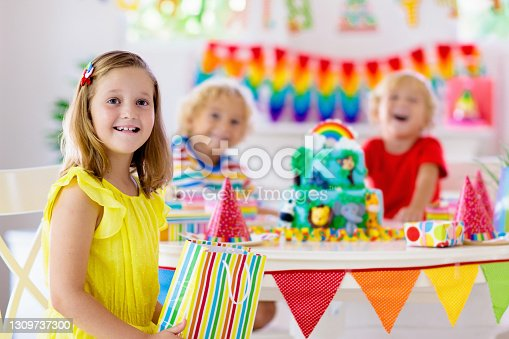 istock Child birthday party. Kids blow candle on cake. 1309737300