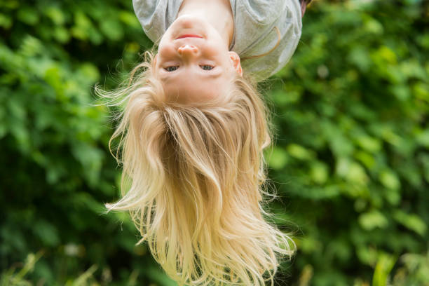 Child blond girl climbing on a rope upside down - summer playground stock photo