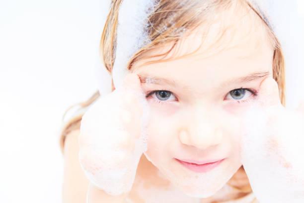 kind blondes mädchen unter bad - mädchen dusche stock-fotos und bilder