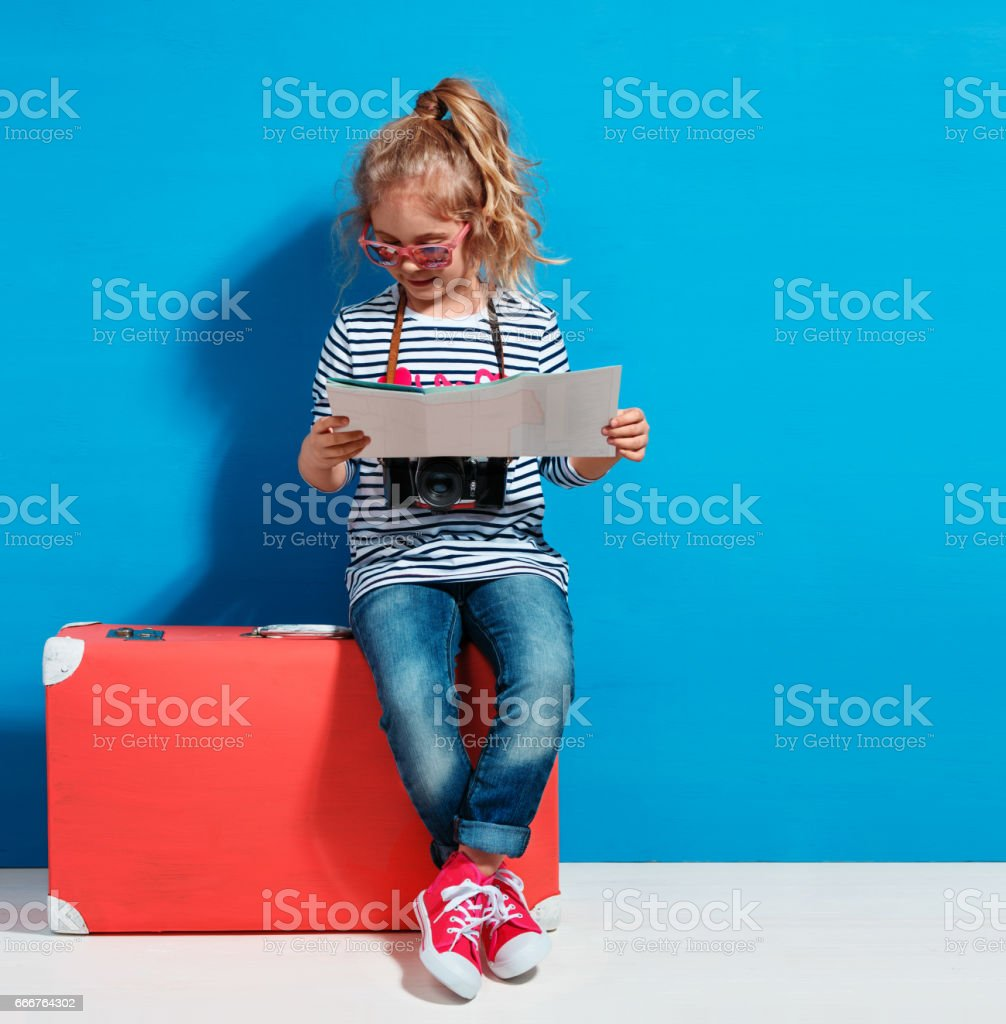 Child blonde girl with pink vintage suitcase and city map ready stock photo
