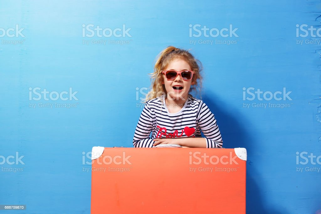 Child blonde girl with pink vintage suitcase ready for summer vacation. Travel and adventure concept foto stock royalty-free