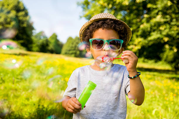 Child blowing bubbles in park stock photo