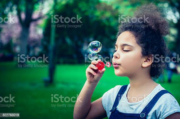 Child ( 7-8 ) Blowing Bubbles in Playground. Stock photo of little girl blowing soap bubbles in playground. Profile shot and natural light.  Shot in Raw and post processed in ProPhoto RGB. No sharpening applied. This file has a  6-7 Years Stock Photo