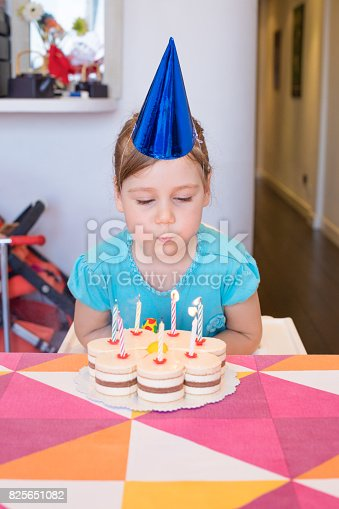 istock child blowing burning candles on birthday cake 825651082