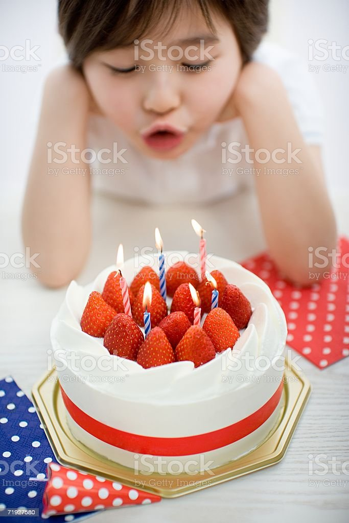 Child blowing out candles on birthday cake royalty-free stock photo