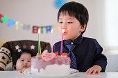 彼の誕生日ケーキのろうそくを吹き、彼の願いを作る子