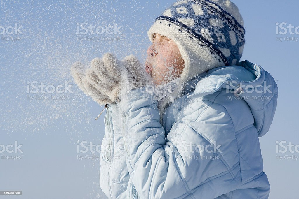 Child blowing snow out of hands stock photo