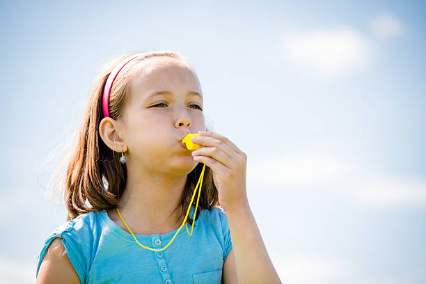 Child blowing whistle stock photo