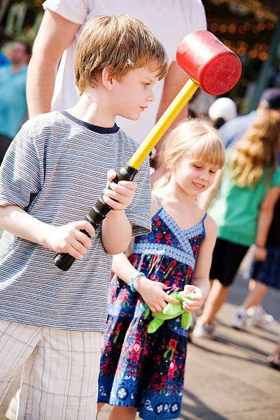 Child Boy and Girl at Fair Playing Hammer Game Lifestyle stock photo