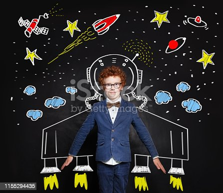 istock Child boy astronaut on blackboard background with space pattern 1155294435