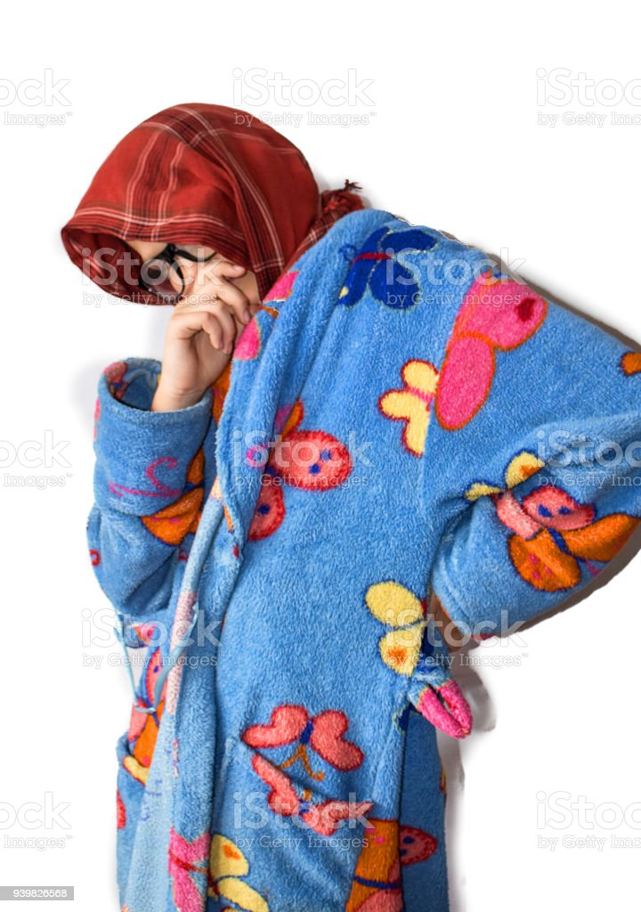 Child boy dressed in grandmother is sad, laughing, posing on white background.  Bathrobe, headscarf, glasses, smile, pensive look. stock photo